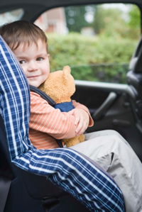 Photo: young boy with a teddy bear in a child safety seat