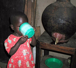 A young girl drinks safe water from a SWS storage vessel in her home.