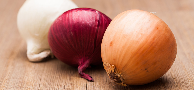Photo of 3 different colored onions on a board.