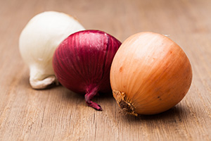 Various onions on a wooden table.