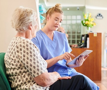 Photo of a patient navigator helping a patient schedule an appointment.