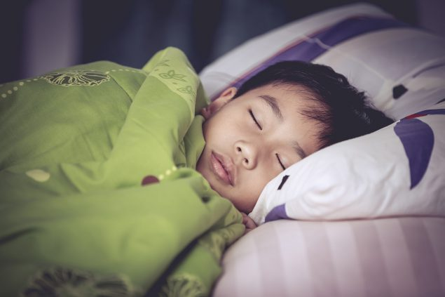 Photo of a child in a bed sleeping.