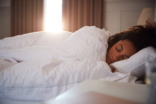 Photo of Peaceful Woman Asleep In Bed As Day Break Through Curtains