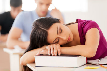 Photo of an adolescent girl asleep on her desk.