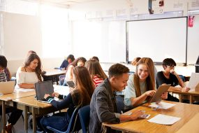 High School Students Sitting At Desks In Classroom Using Laptops