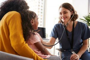 Female Pediatrician Wearing Scrubs Listening To Girls Chest With Stethoscope In Hospital Office