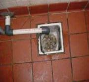 Desagüe del piso tapado con desechos, agua en el piso de la cocina