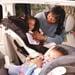 Madre ajustando el cinturón de seguridad de su hijo