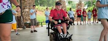 Joven en silla de ruedas rodeado de niños