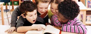 Cuatro niños viendo un libro