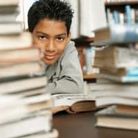 Joven estudiante entre pilas de libros