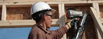 Un trabajador de la construcción con una pistola de clavos