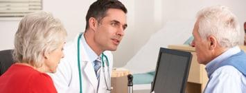 Un hombre y una mujer consultan a su profesional de cuidados de salud