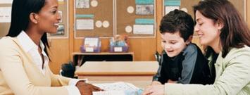 Una profesora hablando con una madre y su hijo