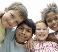 Cuatro estudiantes con la maestra en un salón