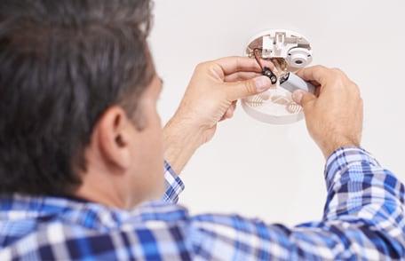 un hombre cambiando batería en detector de monóxido