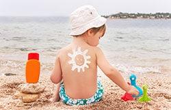 Protector solar en forma de sol sonriente en la espalda de un niño.