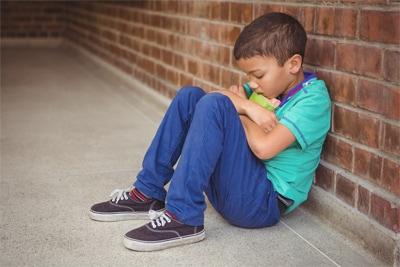 Un niño triste que está sentado contra una pared.