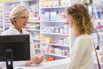 Una farmacéutica habla con un paciente sobre una receta.