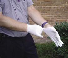 Fotografía de un trabajador mientras se pone guantes de látex