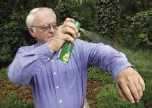Fotografía de un hombre mientras aplica repelente de mosquitos en su ropa