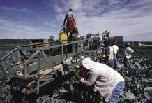Fotografía de trabajadores al aire libre con camisas de manga larga y pantalones largos