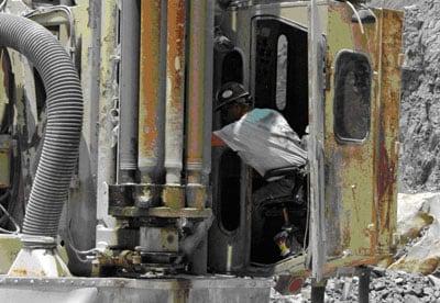Figura 1 – Operador del taladro asomándose por la puerta de la cabina abierta para dirigir la colocación de un nuevo taladro.