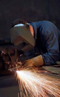 1. Hombre que lleva mascara de soldadura mientras trabaja y las chispas estallan