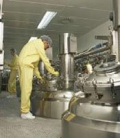 3. Un hombre que lleva traje amarillo para protejer contra productos químicos que gira la rueda de una máquina.