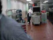 1.1 Hombre lavando platos en una cocina con agua regada por el piso