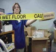 Persona sosteniendo cinta adhesiva amarilla de aviso de que el piso está mojado