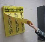 Mano sacando una toalla amarilla de seguridad de un dispensador de almohadillas para secar derrames montado en la pared