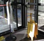 Gancho con bolsas para sombrillas y dispensador de almohadillas absorbentes para secar derrames en la entrada al vestíbulo de un edificio
