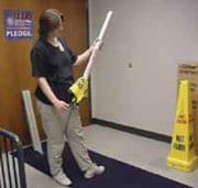 Persona sosteniendo una señal de piso mojado plegable