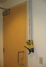 Tubo para guardar las señales de piso mojado plegables montado en una pared cerca de una puerta