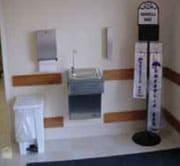 Área con dispensador de bolsas para sombrillas, fuente de agua, dispensador de toallas de papel y canasta para basura