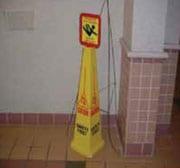 Señal de piso mojado amarilla en forma de cono con una señal de advertencia pues-ta en la parte de arriba
