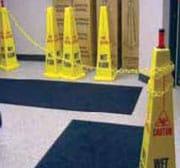 Cadena amarilla de seguridad colgada entre dos señales de piso mojado amarillas en forma de cono