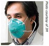 Trabajador de la salud con un estetoscopio en los oídos, usando un respirador con mascarilla de filtrado.