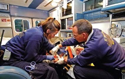 Dos paramédicos, vistos de perfil y sentados en una ambulanza, que ponen un tubo intravenoso en un paciente.
