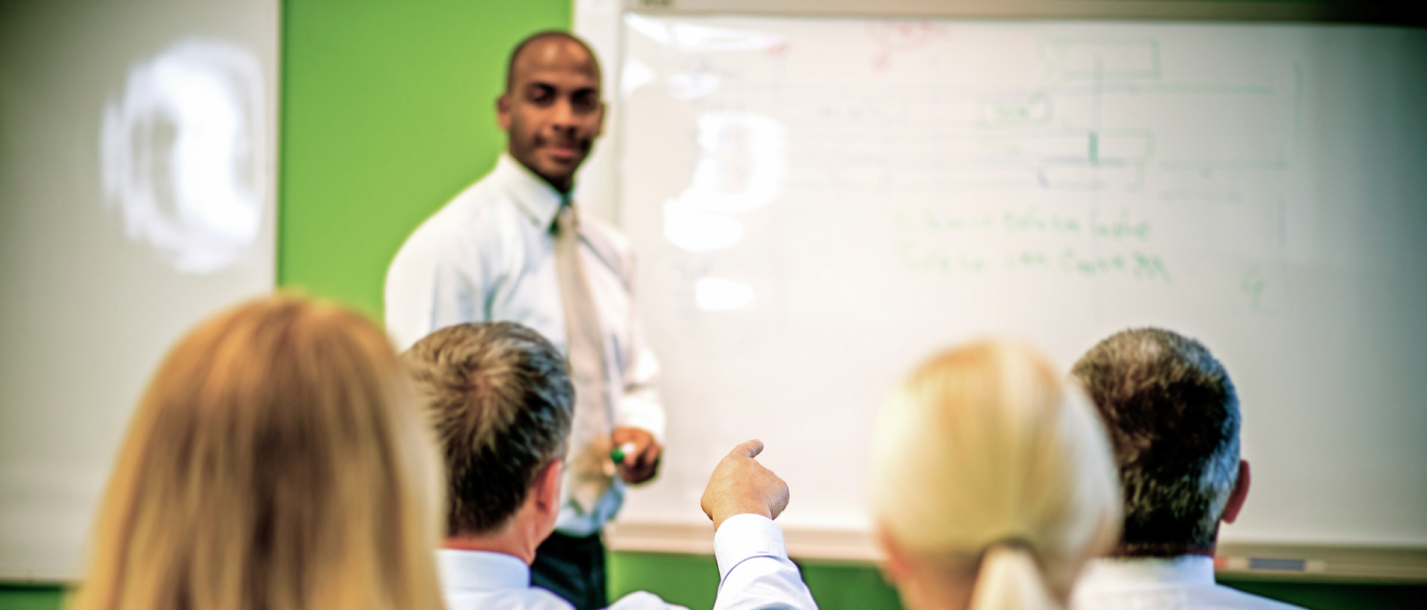A man teaches a class of adults. A student points at the board and makes a comment.