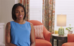 Black Female sitting in room with window and chair behind her talking to camera