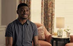 Black male sitting in room with window and chair behind him talking to camera