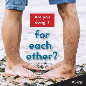 Image displays the lower legs of two men facing each other while standing barefoot on a rocky beach, along with the following text:  Are you doing it for each other?