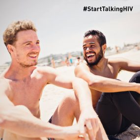 Image displays two men smiling/laughing while sitting on a beach.