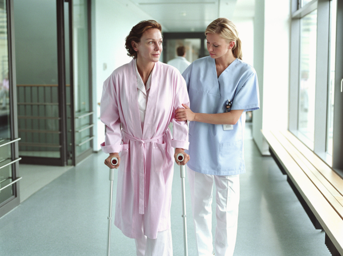 A woman using crutches to walk with the aid of a nurse.