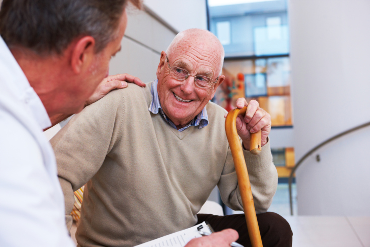 Man with a cane smiling at his doctor.