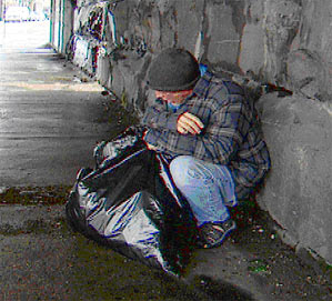 Image of a homeless man on the street with a garbage bag.