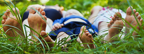A family's bare feet on grass