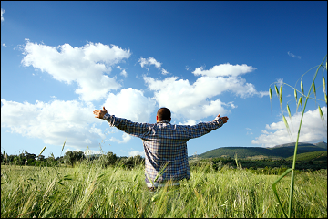 Man with arms outstretched in a field